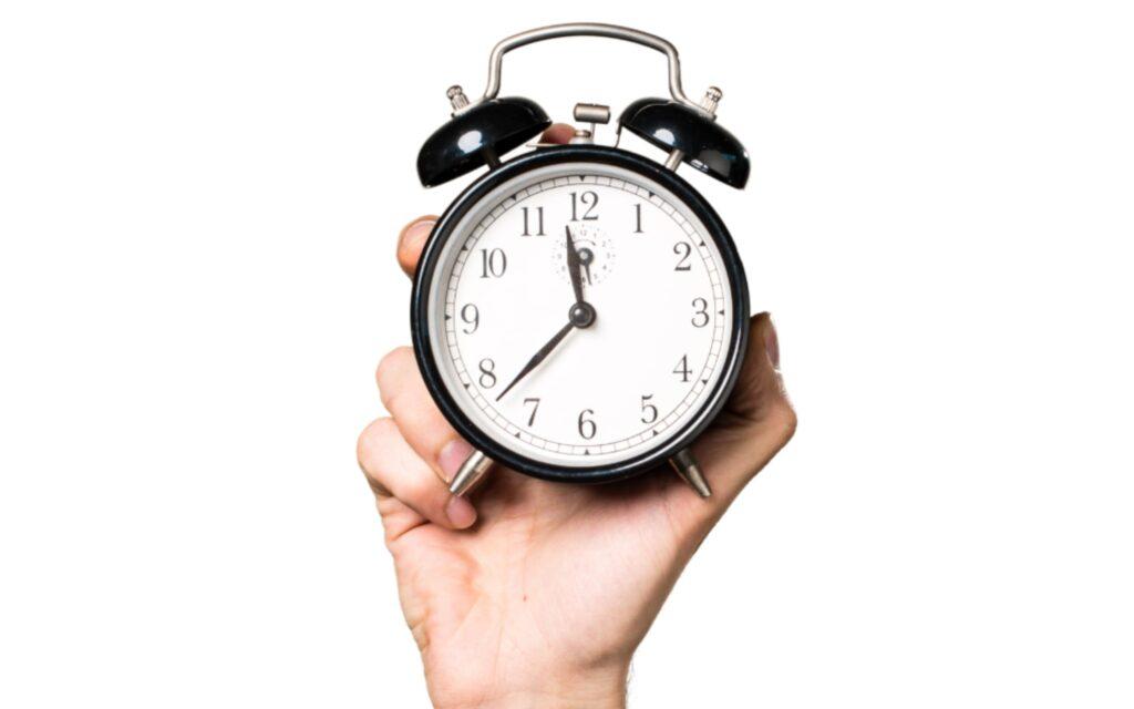Ilustracja przedstawiająca rękę trzymającą zegarek